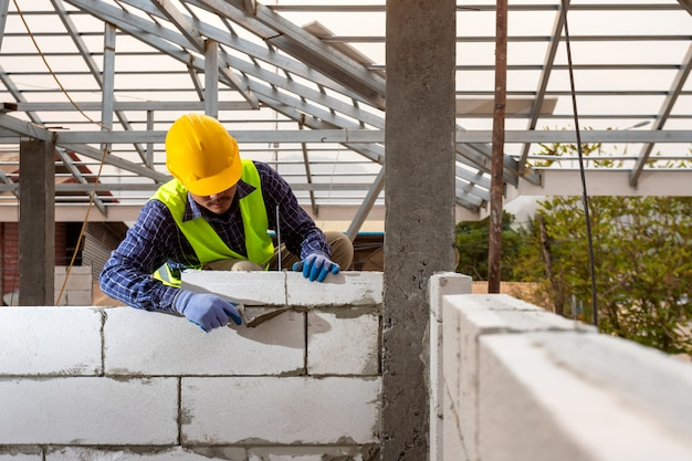 Constructor de albañiles trabajando con bloques de hormigón celular autoclavado. muros, instalación de ladrillos en obra, conceptos de ingeniería y construcciones.