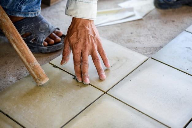 Constructor de azulejos por trabajador de la construcción.