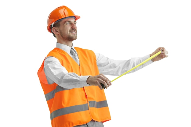 El constructor en un chaleco de construcción y casco naranja de pie en estudio blanco