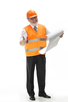 El constructor en un chaleco de construcción y casco naranja de pie en la pared blanca del estudio