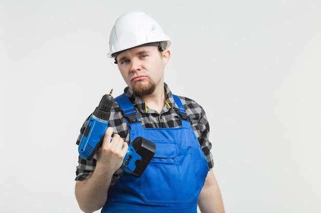 Constructor divertido de pie con destornillador sobre fondo blanco.