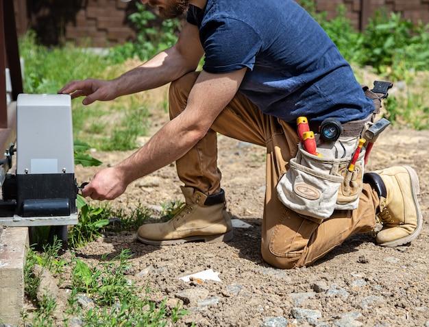 Constructor de electricista en el trabajo, dando servicio al cuadro de distribución industrial del fuselaje. profesional en monos con herramienta de electricista.