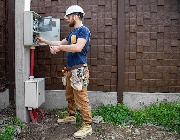 Constructor electricista en el trabajo, examina la conexión del cable en la línea eléctrica en el fuselaje de un cuadro de distribución industrial. profesional en monos con herramienta de electricista.