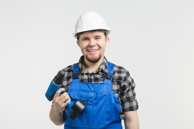 Constructor feliz de pie con un destornillador en la pared blanca
