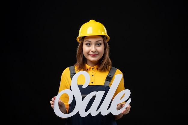 Constructor femenino de vista frontal con cartel de venta blanco sobre pared negra