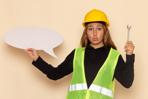 Constructor femenino de vista frontal en casco amarillo sosteniendo un gran cartel blanco con herramienta plateada en la pared blanca femenina