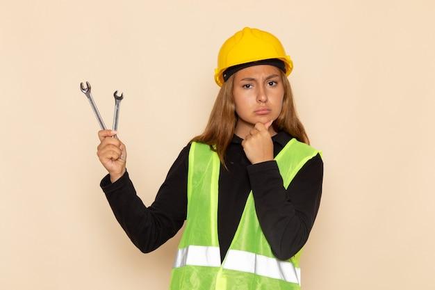 Constructor femenino de vista frontal en casco amarillo sosteniendo instrumentos de plata en el escritorio blanco arquitecto femenino