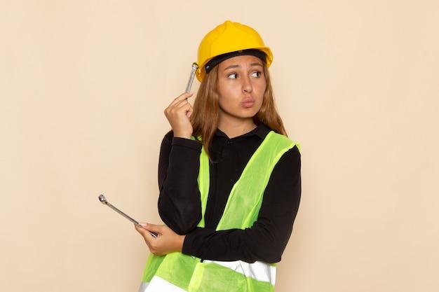 Constructor femenino de vista frontal en casco amarillo sosteniendo instrumentos de plata pensando en la pared blanca arquitecto femenino