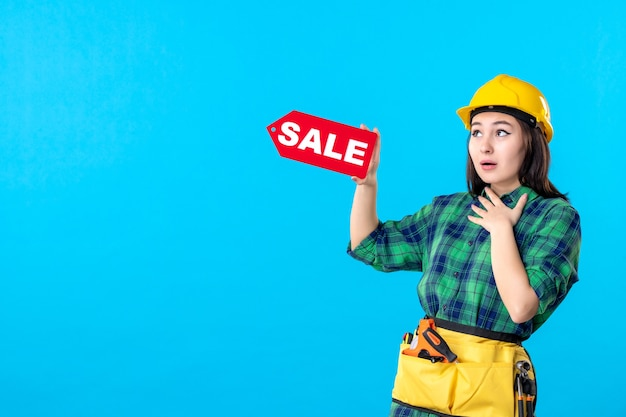 Constructor femenino de la vista frontal que sostiene la escritura roja de la venta en azul