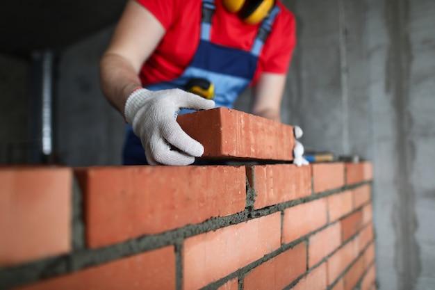 Constructor hace un ladrillo de una pared en un apartamento