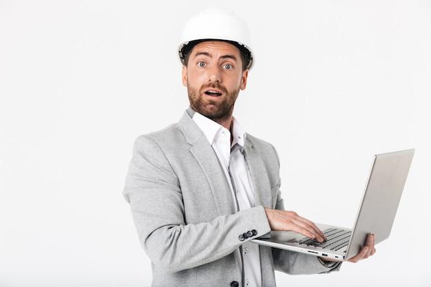 Constructor de hombre barbudo confundido vistiendo traje y casco que se encuentran aisladas sobre la pared blanca, mostrando la computadora portátil