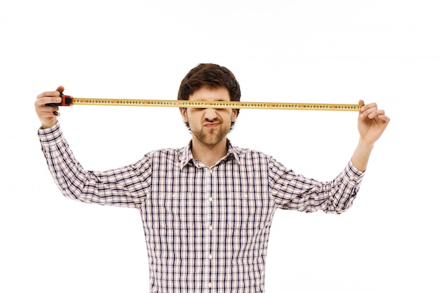 Constructor de hombre divertido, cinta métrica abierta sobre los ojos