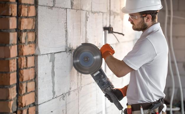 El constructor industrial trabaja con una amoladora angular profesional para cortar ladrillos y construir paredes interiores. electricista.