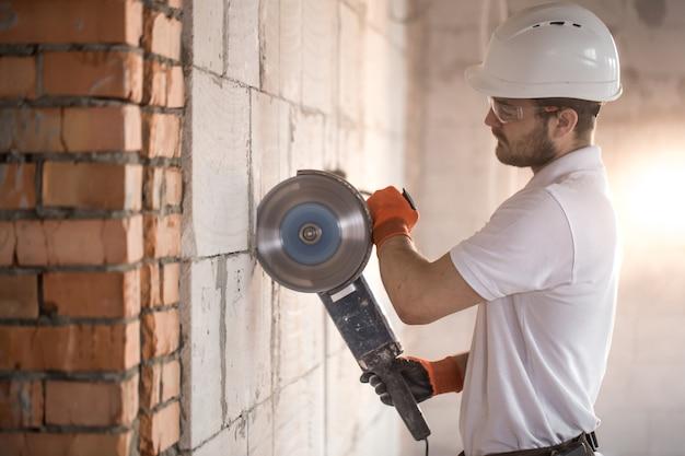 El constructor industrial trabaja con una amoladora angular profesional para cortar ladrillos y construir paredes interiores.