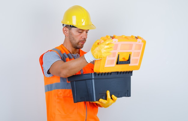Constructor masculino abriendo caja de herramientas de plástico en uniforme, casco, guantes, vista frontal.
