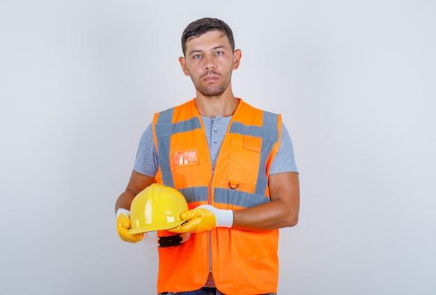 Constructor masculino con casco en sus manos en uniforme, jeans, guantes, vista frontal.
