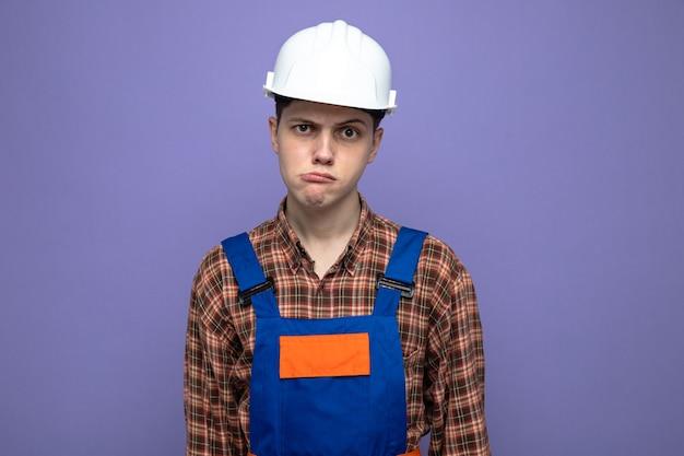 Constructor masculino joven disgustado vistiendo uniforme