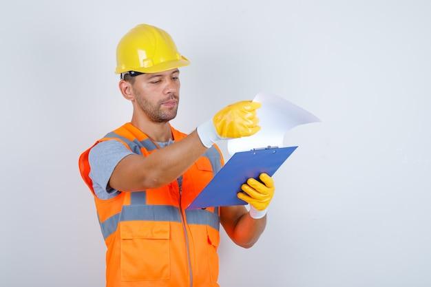 Constructor masculino mirando a través de bocetos en papel en uniforme, casco, guantes, vista frontal.