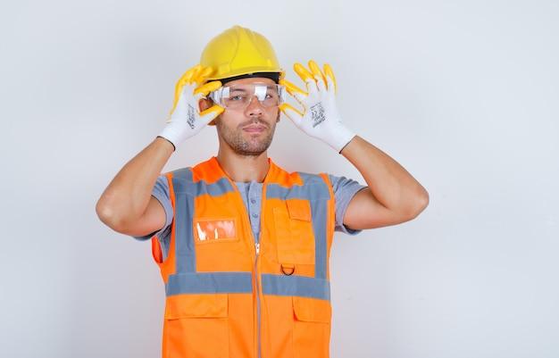 Constructor masculino en uniforme, casco, guantes con gafas de seguridad, vista frontal.