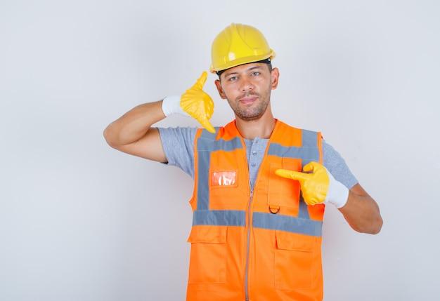 Constructor masculino en uniforme, casco, guantes que muestran el gesto de llamarme o de contacto y mirar confiado, vista frontal.