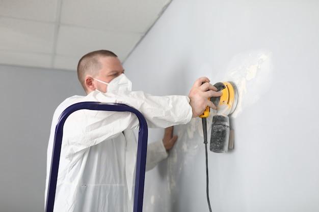 El constructor masculino en uniforme limpia la pared con masilla