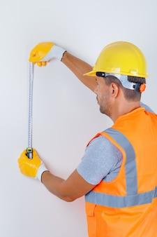 Constructor masculino usando cinta métrica en uniforme, casco, guantes y mirando ocupado, vista posterior.