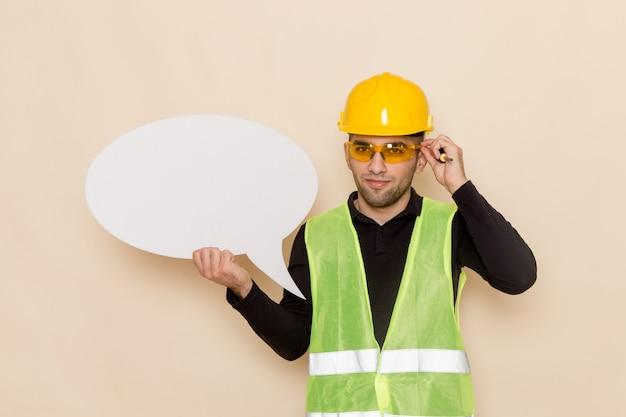 Constructor masculino de vista frontal en casco amarillo con cartel blanco en el escritorio de luz