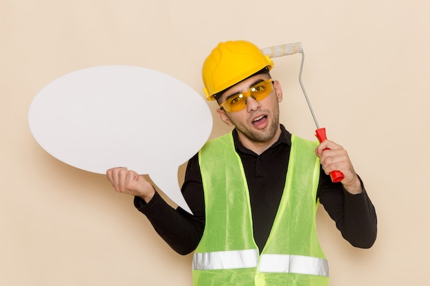 Constructor masculino de vista frontal en casco amarillo con cartel blanco y pincel sobre el fondo claro