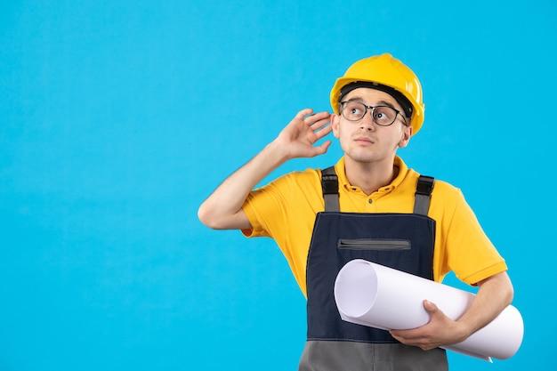 Constructor masculino de vista frontal en uniforme amarillo con plan de papel en azul