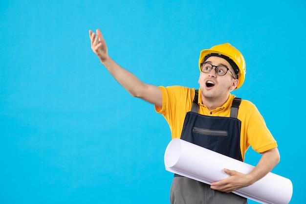 Constructor masculino de vista frontal en uniforme con plan de papel en azul