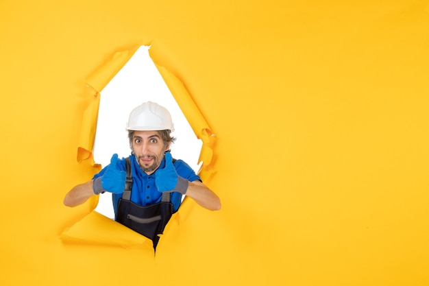 Constructor masculino de vista frontal en uniforme sobre fondo amarillo