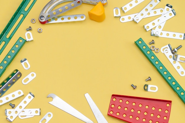 Constructor de metal, hierro sobre fondo amarillo. diseñador de piezas de metal para niños para modelar.