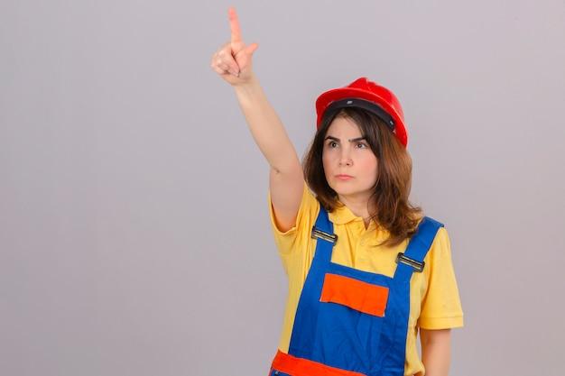 Constructor mujer en construcción uniforme y casco de seguridad mirando a un lado apuntando hacia arriba con el dedo con expresión enojada en la cara sobre la pared blanca aislada