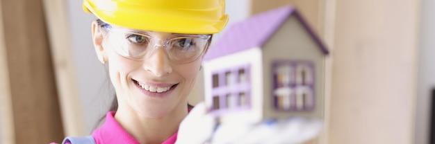 Constructor de mujer sonriente sosteniendo casa en sus manos