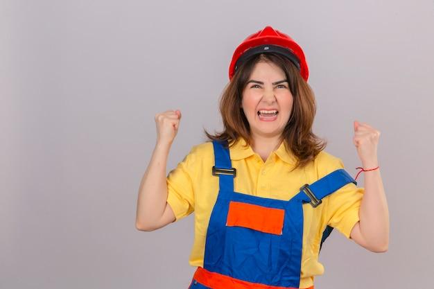 Constructor mujer vestida con uniforme de construcción y casco de seguridad enojado y enojado levantando puños frustrados y furiosos gritos con cara de enojo sobre la pared blanca aislada
