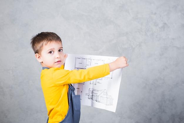 Constructor de niño sosteniendo papel con proyecto.