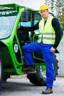 Constructor o conductor de pie delante de maquinaria de construcción en obra