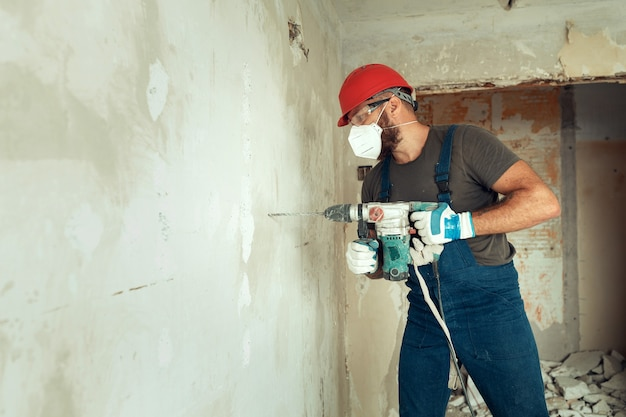 Constructor con perforador perfora agujeros en muro de hormigón