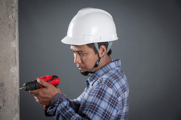 Constructor que sostiene el taladro sobre fondo gris