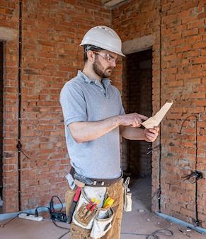 Un constructor en ropa de trabajo examina un dibujo de construcción en un sitio de construcción
