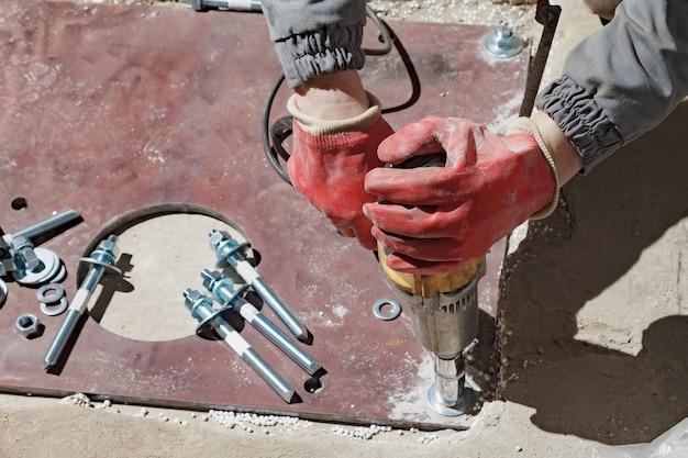 El constructor rota las tuercas con una llave eléctrica.