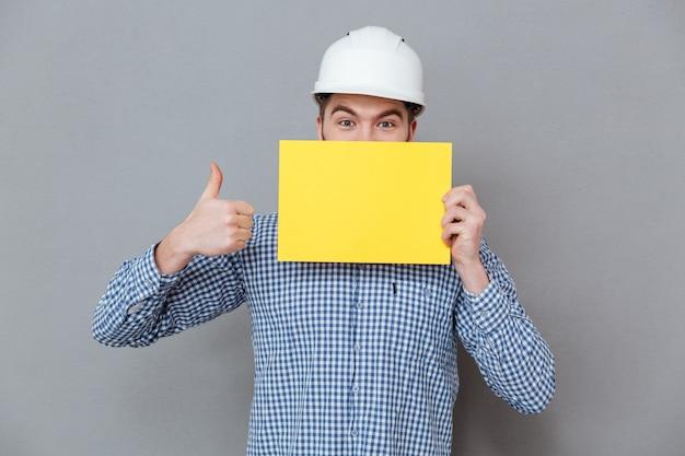 Constructor sosteniendo en blanco en blanco hacer pulgares arriba gesto