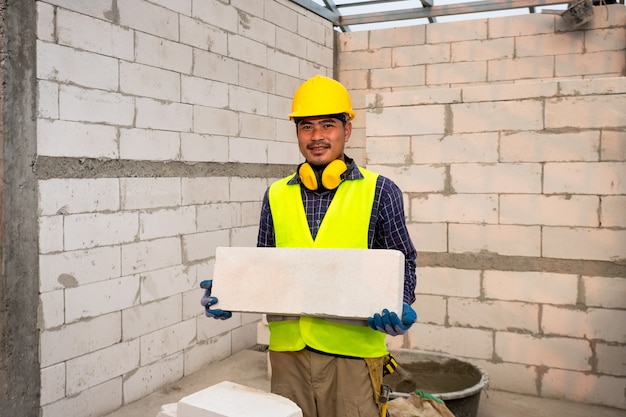 El constructor sostiene ladrillos aireados en autoclave. el concepto propone utilizar ladrillos aireados en autoclave en la construcción de casas.