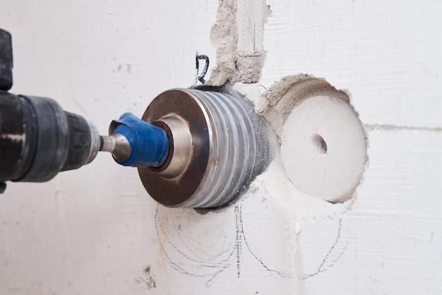 Constructor con taladro perforador hummer perfora un agujero en la pared