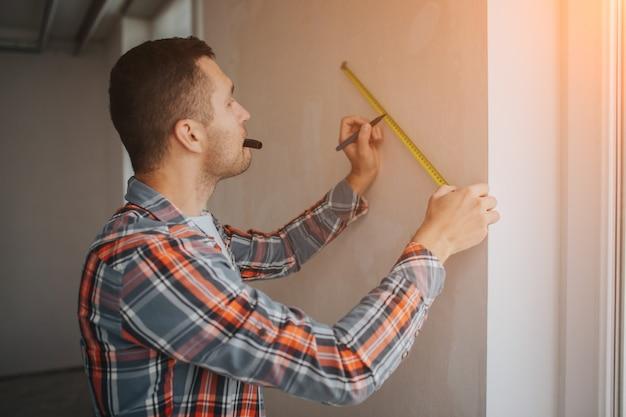 El constructor trabaja en el sitio de construcción y mide la pared. trabajador en un casco de construcción naranja hace reparaciones en la casa