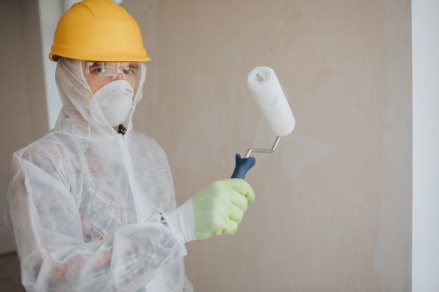 El constructor trabaja en el sitio de construcción. trabajador con un rodillo de pintura. lleva un traje protector y una máscara para una cara.