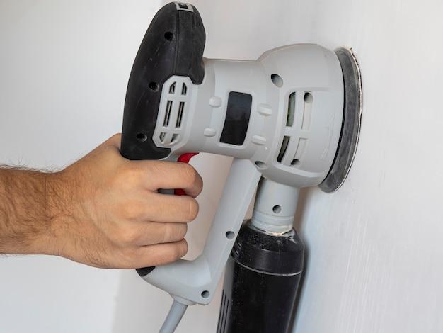 Un constructor usa una lijadora para procesar un muro de hormigón blanco. concierto de construcción