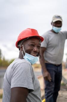 Constructores afroamericanos que usan cascos y máscaras faciales mientras trabajan