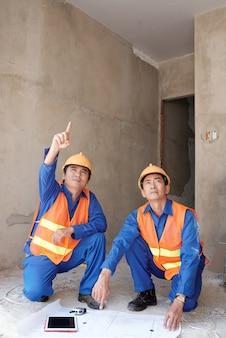 Los constructores despliegan el plan de construcción en el piso para encontrar qué pared soporta la carga