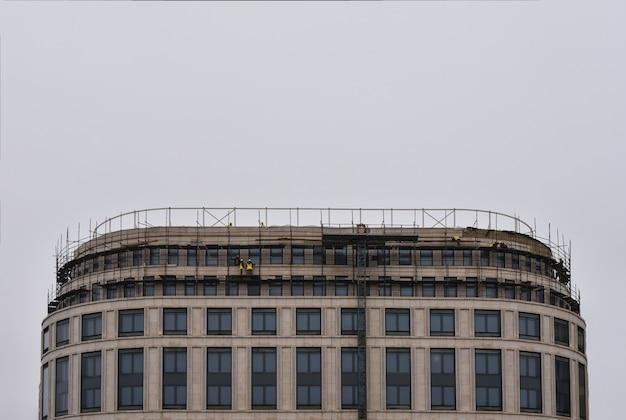 Los constructores están construyendo el techo de un edificio de gran altura, copyspace.